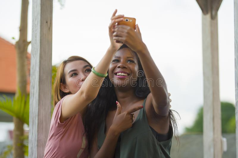 Young happy and beautiful black afro American woman enjoying holidays at tropical resort with Asian girlfriend taking selfie. Young happy and beautiful black royalty free stock photography