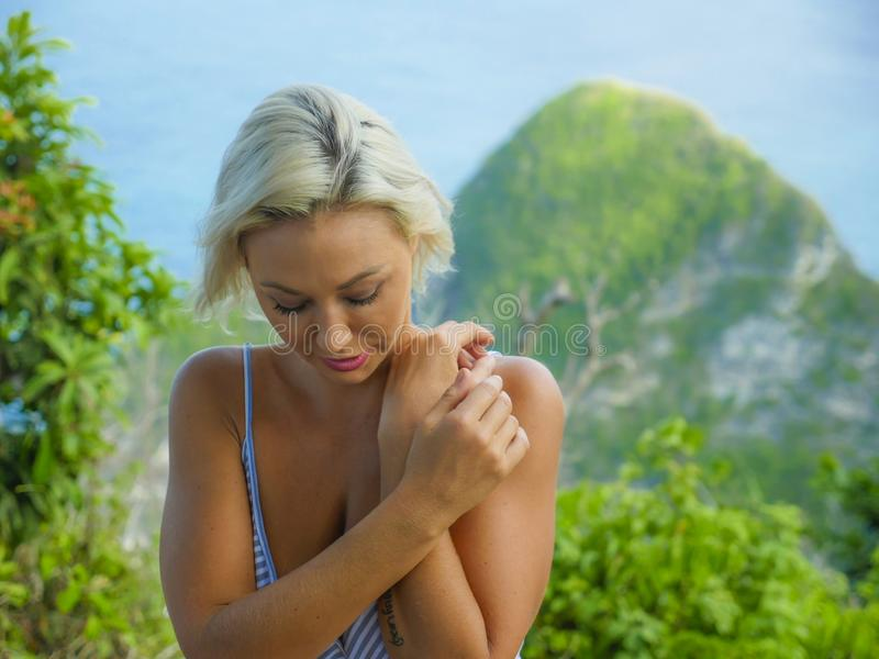 Young happy and beautiful blond woman relaxed feeling sea breeze at tropical beach cliff landscape enjoying Summer holidays stock photography