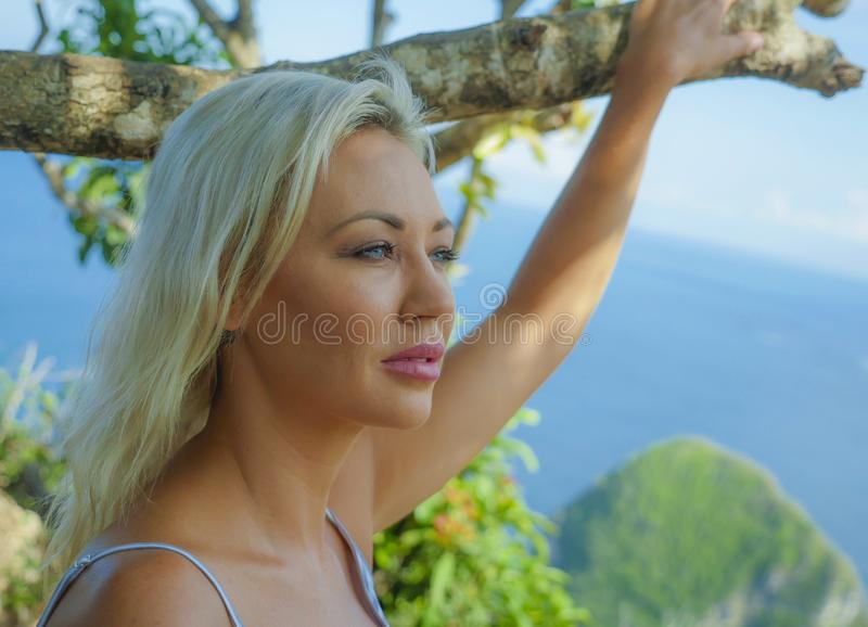 Young happy and beautiful blond woman relaxed feeling sea breeze at tropical beach cliff landscape enjoying Summer holidays stock image