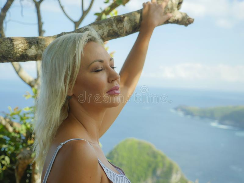 Young happy and beautiful blond woman relaxed feeling sea breeze at tropical beach cliff landscape enjoying Summer holidays royalty free stock photos