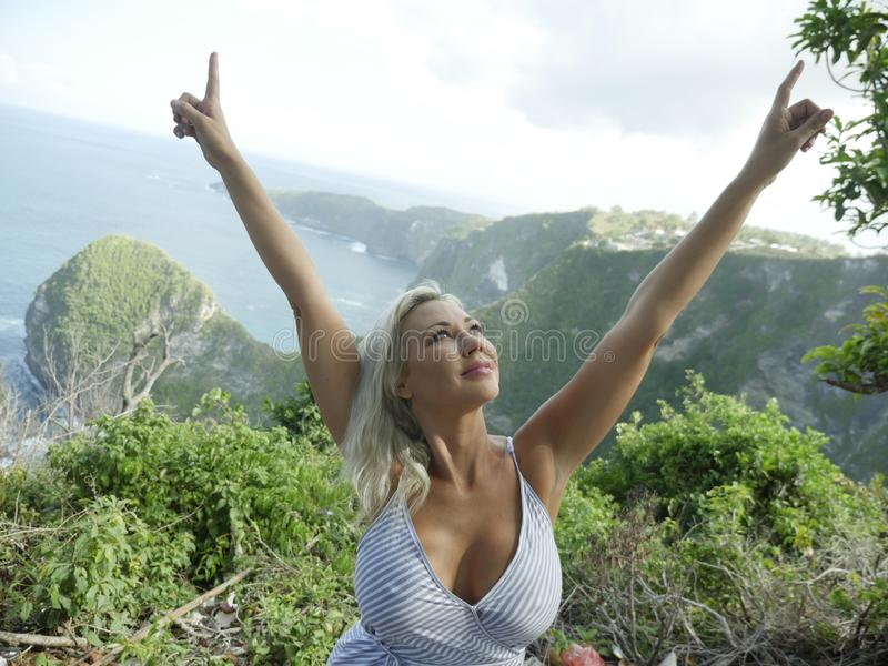 Young happy and beautiful blond woman relaxed at tropical beach cliff landscape enjoying Summer holidays getaway carefree at stock images