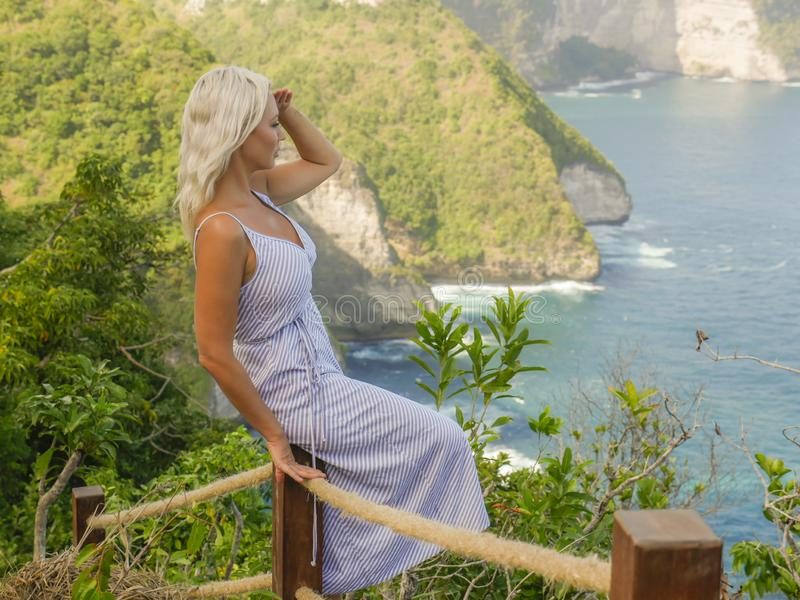 Young happy and beautiful blond woman relaxed at tropical beach cliff viewpoint enjoying Summer holidays getaway carefree at. Paradise island in tourist travel royalty free stock photos