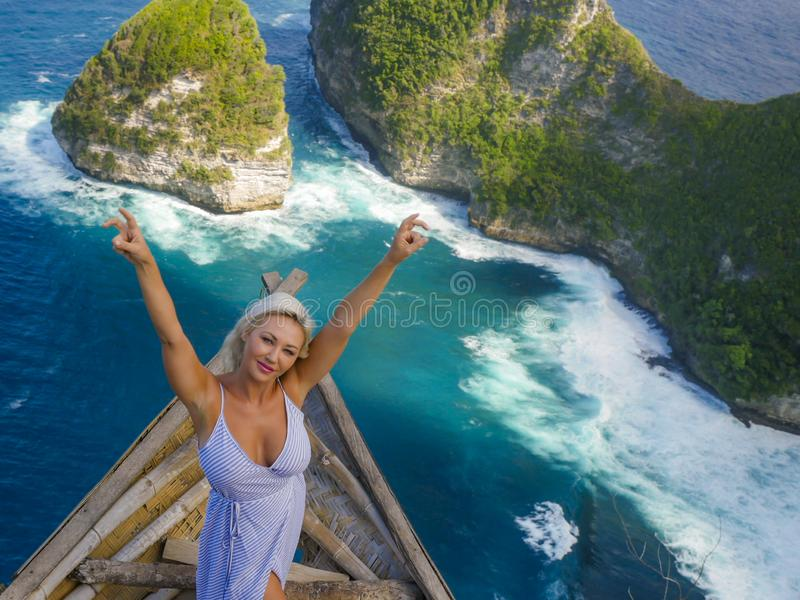 Young happy and beautiful blond woman relaxed at tropical beach cliff viewpoint enjoying Summer holidays getaway carefree at stock images