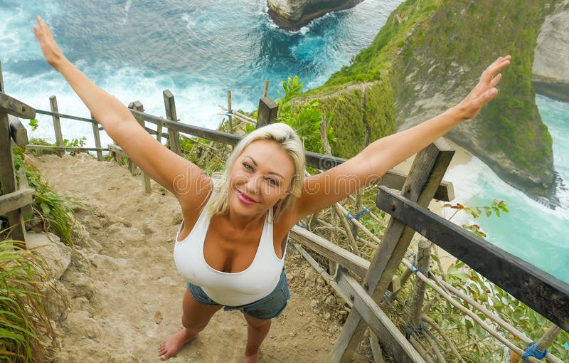 Young happy and beautiful blond woman smiling cheerful at tropical beach cliff landscape enjoying Summer holidays getaway carefree. At paradise island in royalty free stock photos
