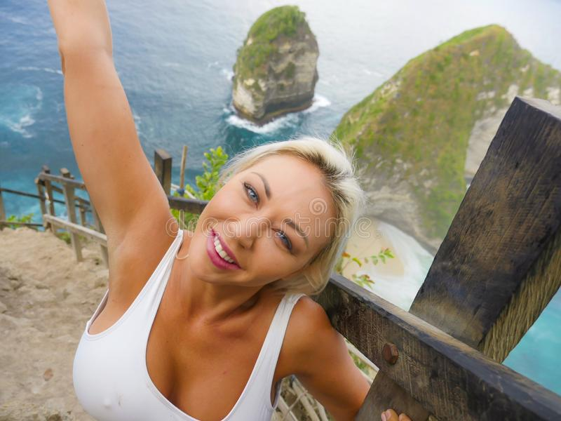 Young happy and beautiful blond woman smiling cheerful at tropical beach cliff landscape enjoying Summer holidays getaway carefree. At paradise island in royalty free stock photography
