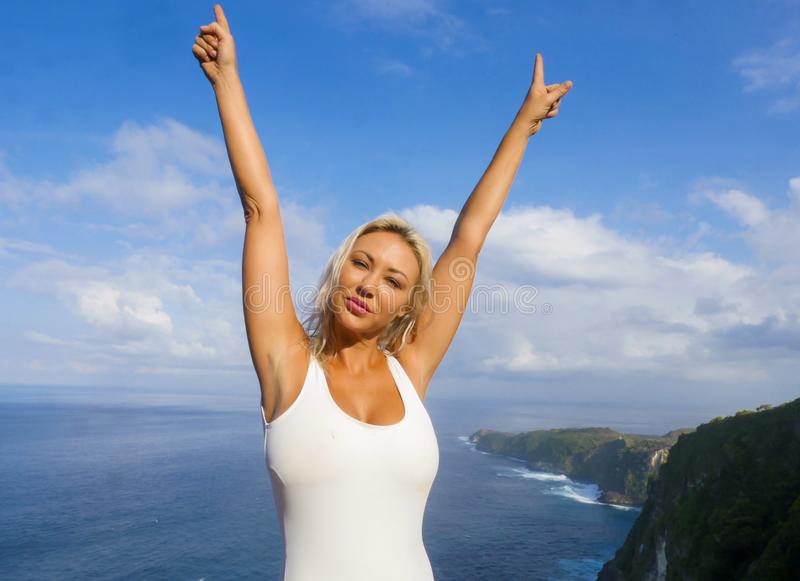 Young happy and beautiful blond woman smiling cheerful at tropical beach cliff landscape enjoying Summer holidays getaway carefree. At paradise island in stock images