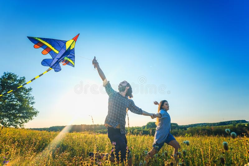 Young happy beautiful couple flying a kite in a summer field, summer happiness and love concept. Young happy beautiful couple flying a kite in a summer field royalty free stock photography