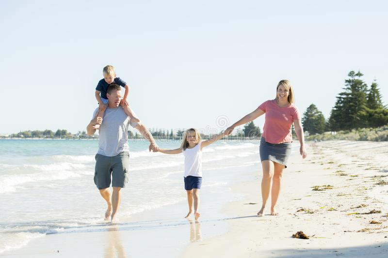 Young happy and beautiful family mother father holding hand of son and daughter walking joyful on the beach enjoying Summer holida stock image