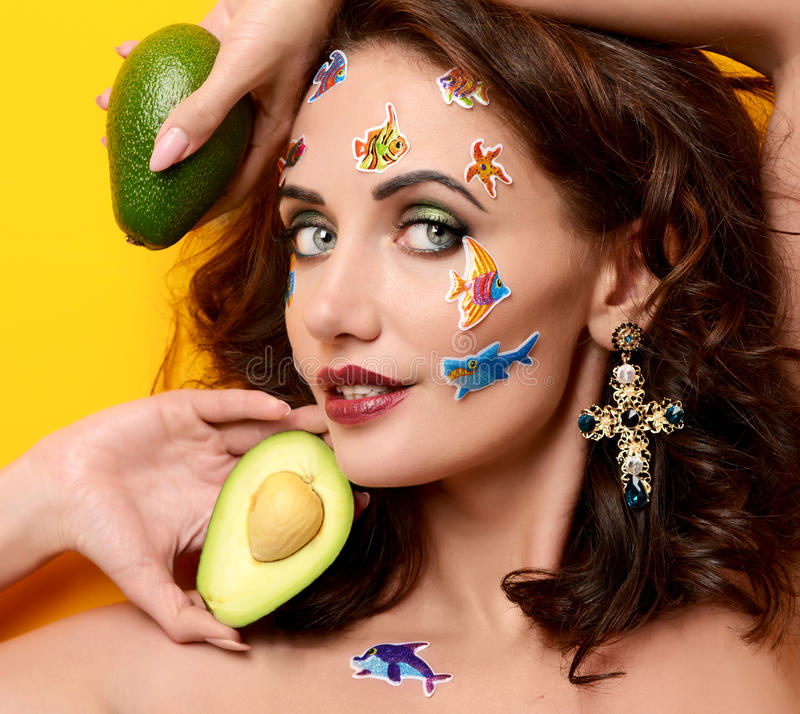 Young happy beautiful fashion curly woman with cartoon fish stickers on face on yellow background. Closeup portrait of young happy beautiful fashion curly woman stock photos