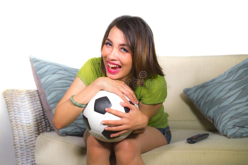 Young happy and beautiful football fan woman watching television game sitting on sofa couch holding soccer ball excited celebratin. Lifestyle portrait at home of royalty free stock images