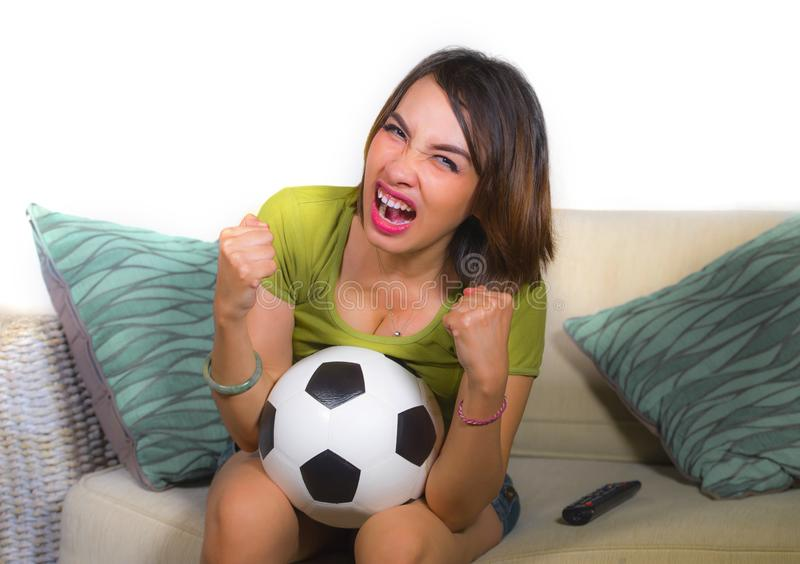Young happy and beautiful football fan woman watching television game sitting on sofa couch holding soccer ball excited celebratin. Lifestyle portrait at home of stock image