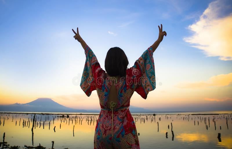 Young happy and beautiful Korean woman in traditional Asian dress at sunrise sea landscape looking away with arms opened feeling f royalty free stock photo