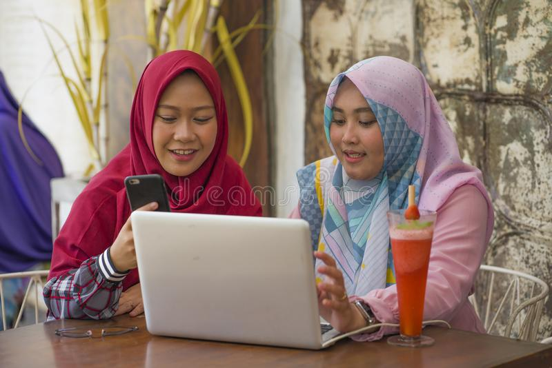 Young happy and beautiful Muslim student women in traditional Islamic hijab head scarf  talking online business working together stock photos