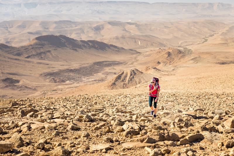 Young pretty woman backpacker ascending stone desert trail, Israel. Young happy beautiful pretty cheerful woman backpacker tourist walking ascending hiking stock photography