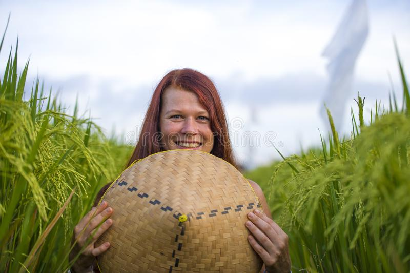 Young happy and beautiful red hair woman playing with traditional Asian farmer hat smiling cheerful isolated on green rice field. In Asia tourist trip and royalty free stock image