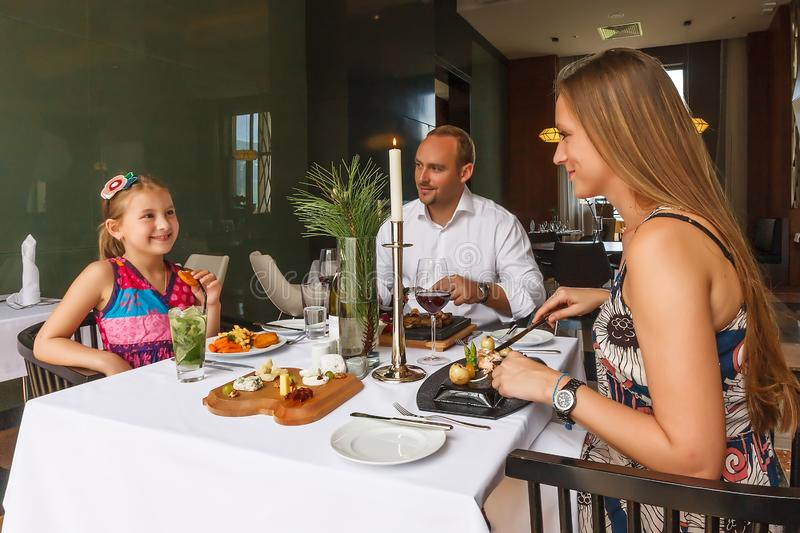 Young happy beautiful smiling Caucasian family of father, mother and daughter enjoying dinner together by served restaurant table. royalty free stock photography