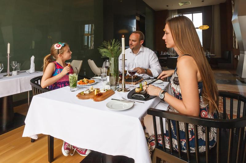 Young happy beautiful smiling Caucasian family of father, mother and daughter enjoying dinner together by served restaurant table stock photos