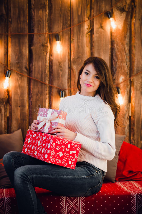 Young happy beautiful woman with gift boxes sits near wall decorated for Christmas in the room of the house. Merry xmas stock photos