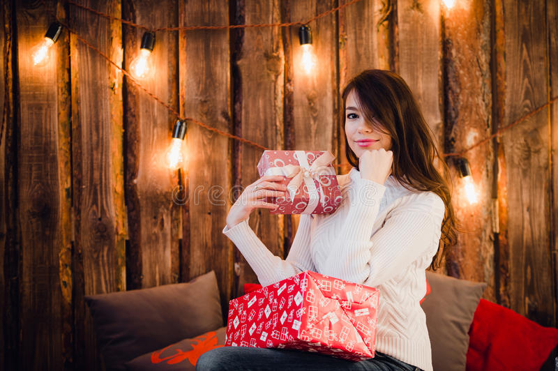 Young happy beautiful woman with gift boxes sits near wall decorated for Christmas in the room of the house. Merry xmas royalty free stock images