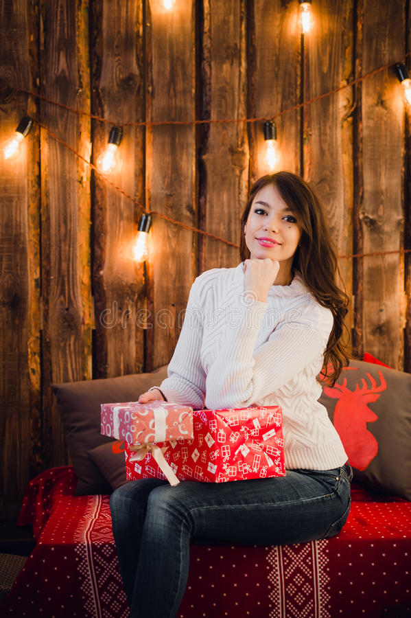 Young happy beautiful woman with gift boxes sits near wall decorated for Christmas in the room of the house. Merry xmas royalty free stock photos