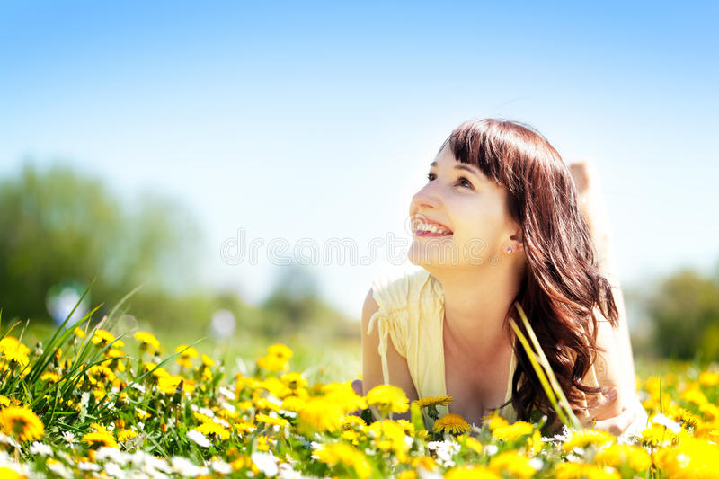 Young happy beautiful woman lying on grass, flowers. Young beautiful woman lying on grass full of spring flowers, looking happy at the sunny blue sky. Happiness stock image