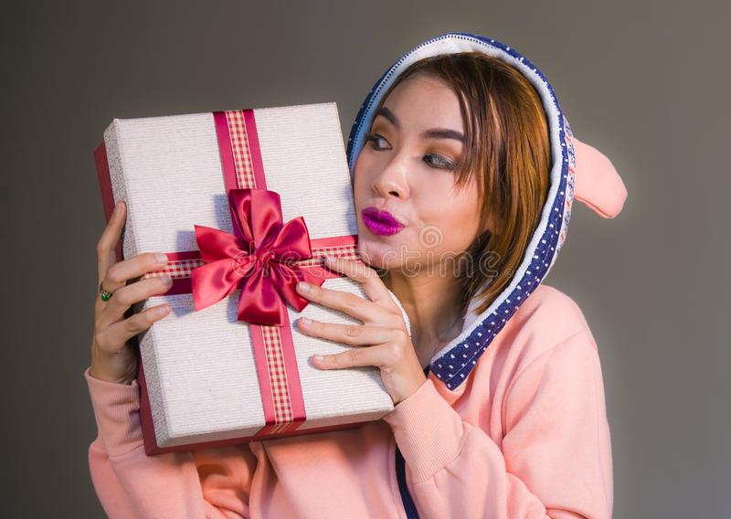 Young happy and beautiful woman in winter warm hoodie holding Christmas or birthday present box with ribbon in her hands smiling c. Heerful and excited royalty free stock images