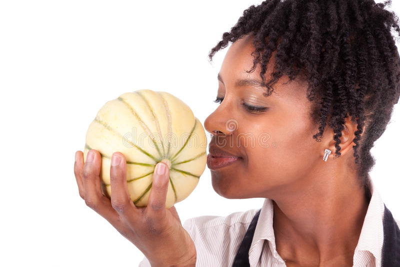 Young happy black / african american woman smelling a fresh melon stock photo
