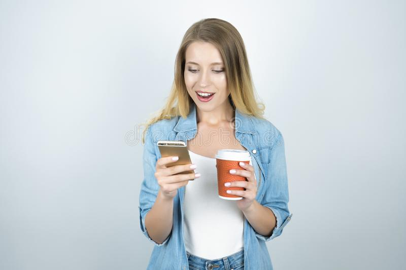 Young happy blond woman holding smartphone in one hand and cup of coffee in another isolated white background royalty free stock photo