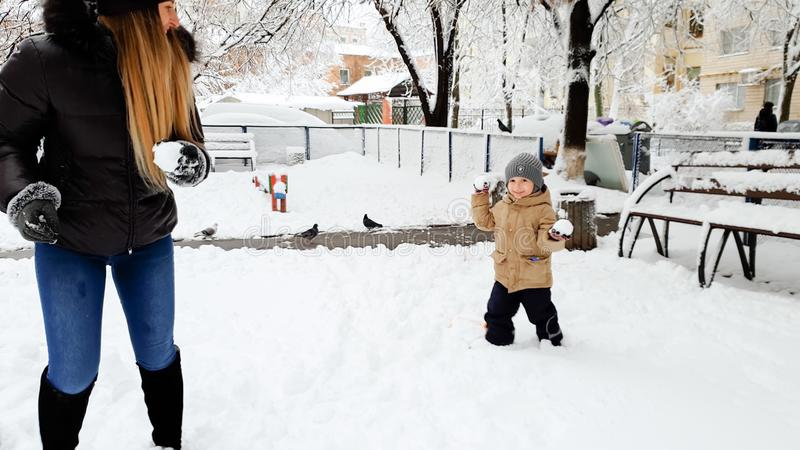 Photo of young happy blond woman playind in snow balls with her cute son in jacket and hat on the playground in the Park stock images