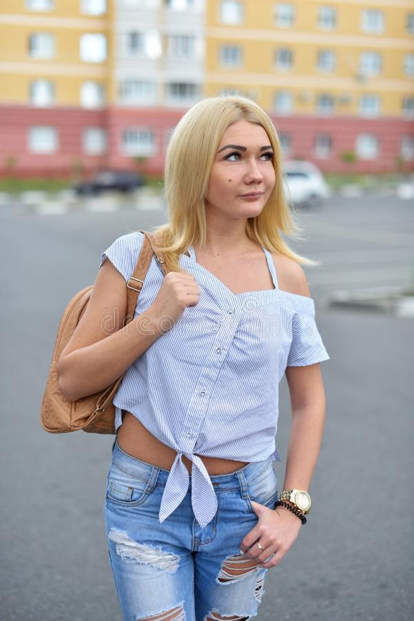 A young and happy blonde girl after dyeing her hair, walking down the street with a backpack in torn blue jeans and smiling. royalty free stock images