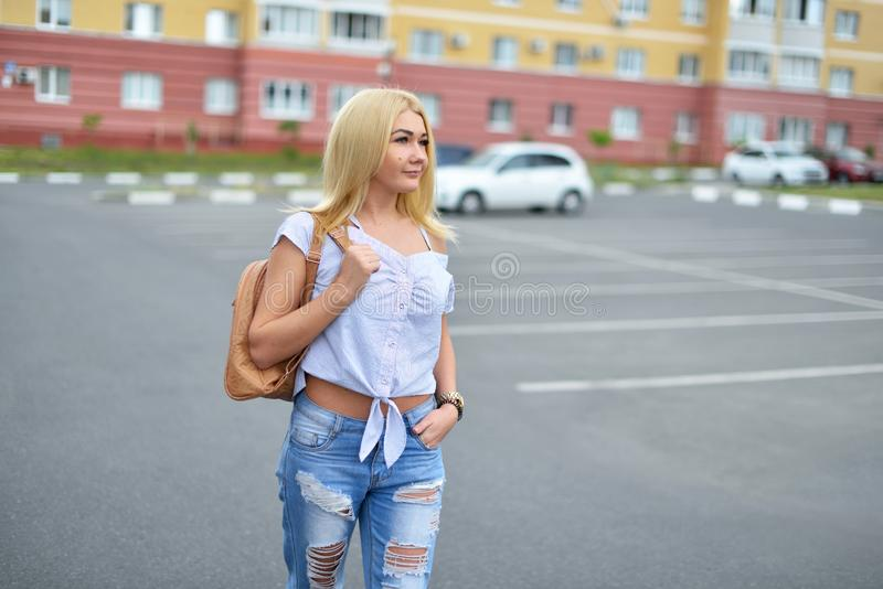 A young and happy blonde girl after dyeing her hair, walking down the street with a backpack in torn blue jeans and smiling. stock photography