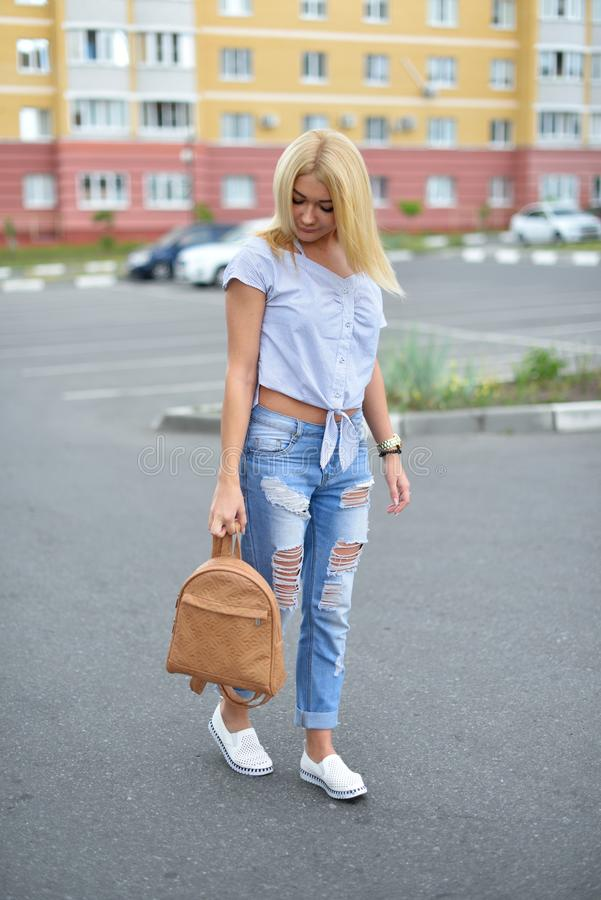 A young girl walks down the street with a beige backpack in torn blue jeans. Fashionable ripped blue jeans on the legs of a teen royalty free stock photography