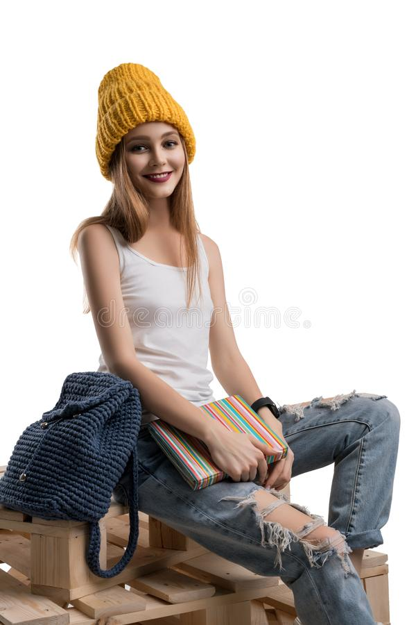 Young happy blonde in knitted hat isolated shot. Young happy blonde in knitted yellow hat, white t-shirt and torn jeans sitting on wooden pallets isolated shot royalty free stock photography