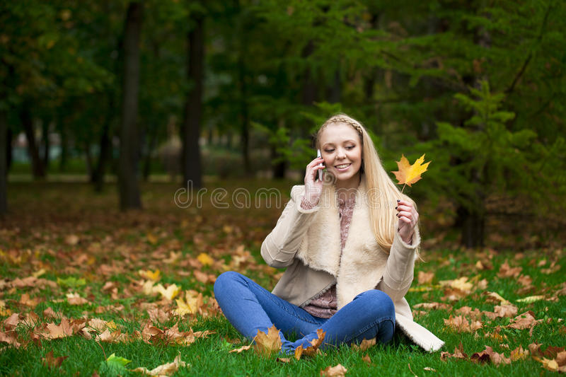 Young happy blonde woman calling by phone in autumn park. Full length, happy blonde woman calling by phone in autumn park stock image
