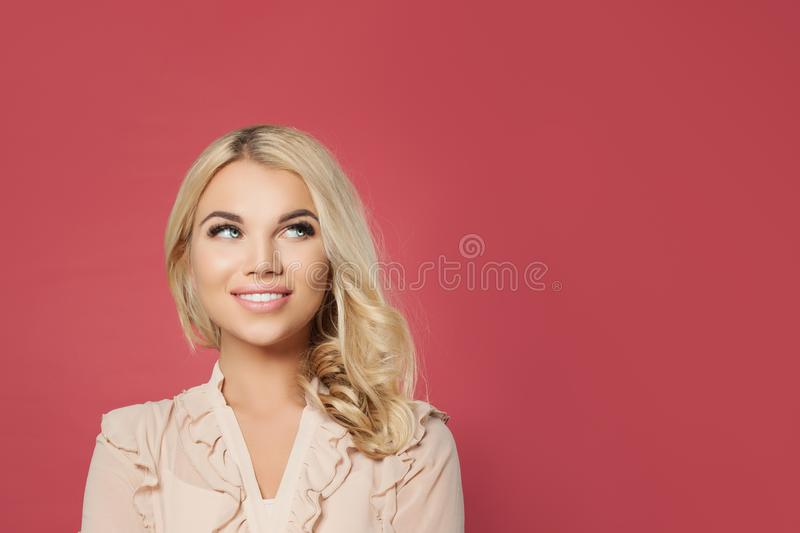 Young happy blonde woman looking up portrait. Cute girl face on pink background stock image