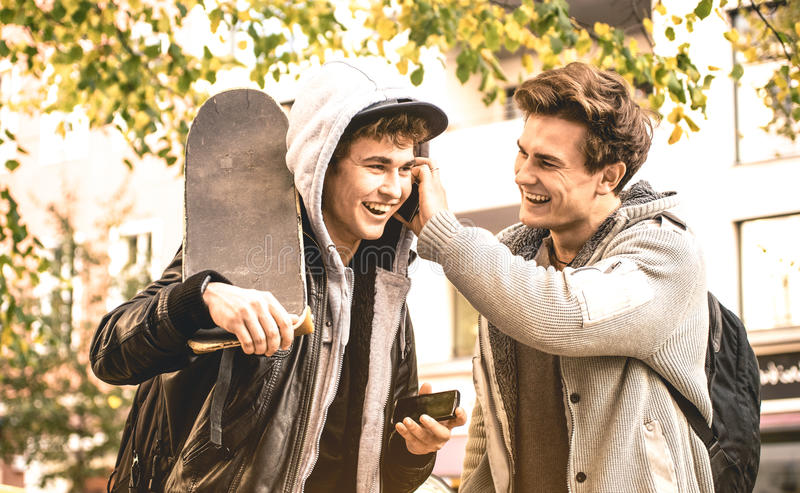 Young happy brothers having fun using mobile smart phones stock photo