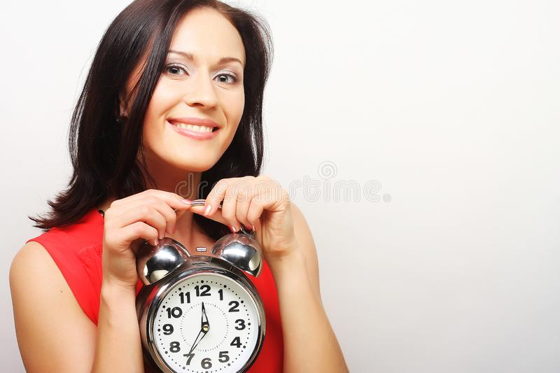 Young happy woman with alarmclock stock photography
