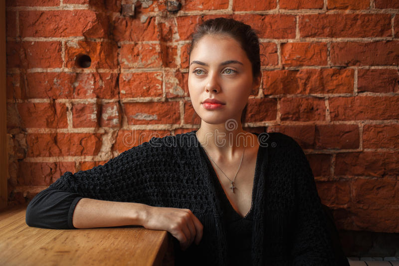 Young happy brunette woman in black boho dress sitting near window against red brick wall at the cafe royalty free stock photo