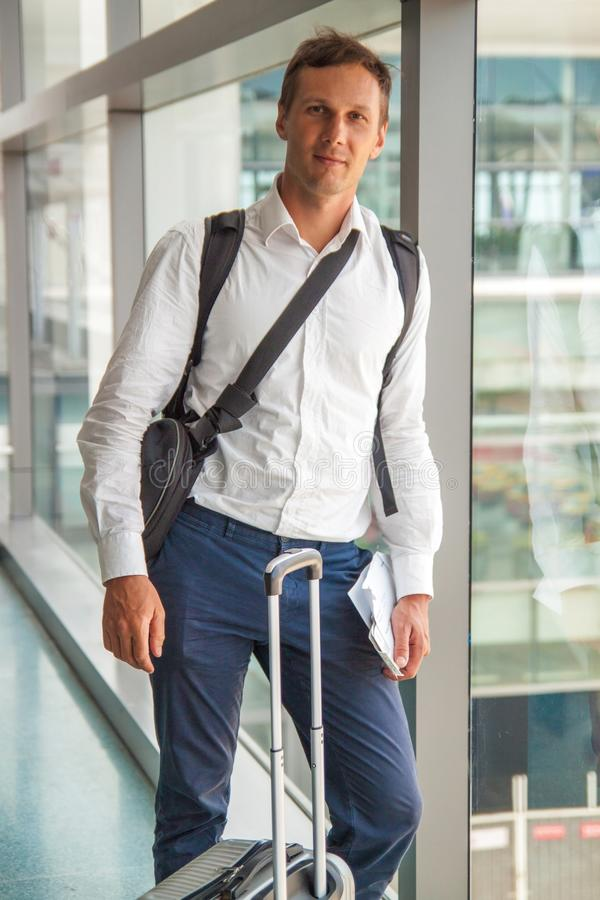 Young happy business man in white shirt waiting for his flight. stock photo