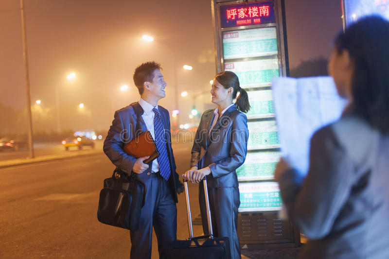 Young happy business people waiting for a bus at night stock photos