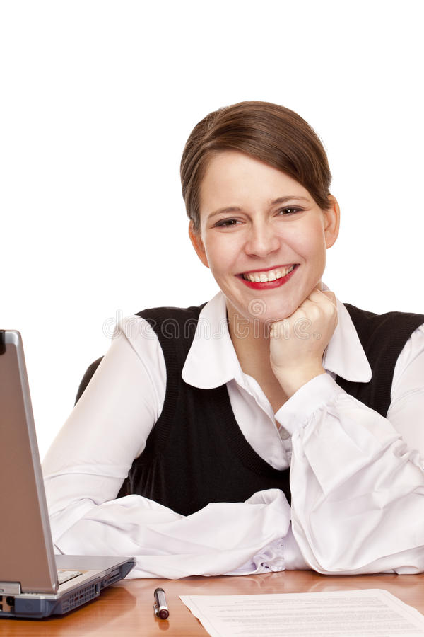 Young happy business woman sits on desk in office stock image