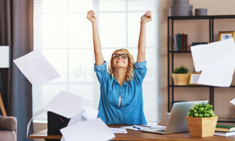 Young happy business woman working on computer and  throws up   papers in   office. Young happy business woman working on computer and  throws up   papers in royalty free stock photo