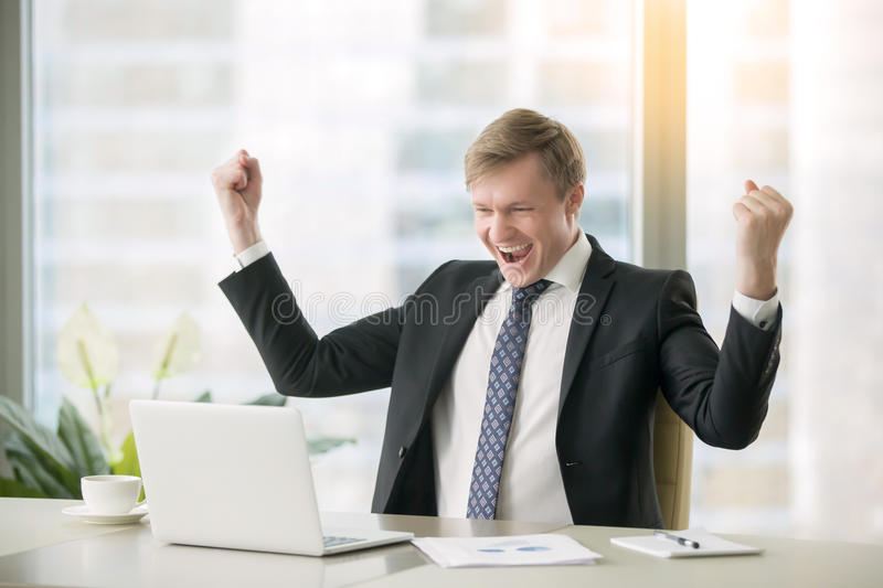 Young happy businessman at the desk. Young happy businessman with really impressive achievements, victory dance, fast growing company, rewarded, won a good stock photo