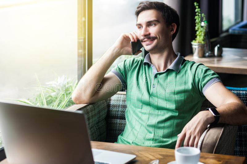 Young happy businessman in green t-shirt sitting at desk with laptop, talking on phone and looking outside and toothy smile royalty free stock photography