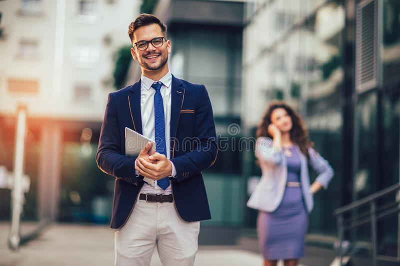 Happy businessman holding digital tablet outside of modern building, businesswoman in background. Young happy businessman holding digital tablet outside of stock photos