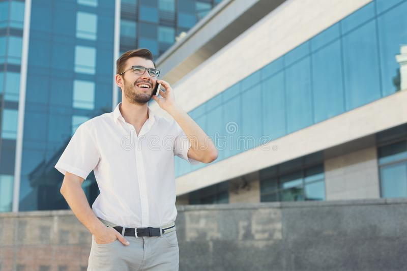 Young happy businessman making a call outdoors royalty free stock photography