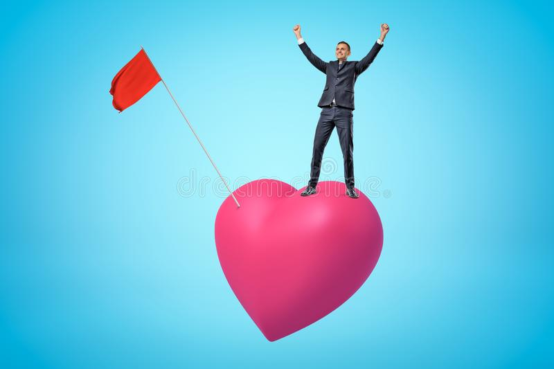 Young happy businessman raising arms up on big pink heart with red flag on blue background. Banking and finance. People and objects. Feelings and emotions stock photo