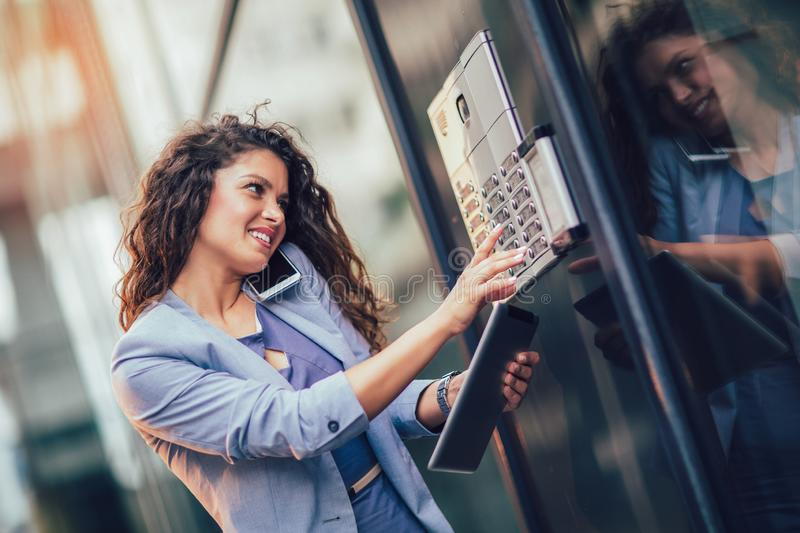 Young happy businesswoman outside the office building, enters the building stock photo