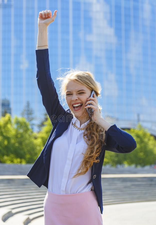 Young happy businesswoman with raised arm talking on phone at street receiving good news royalty free stock images