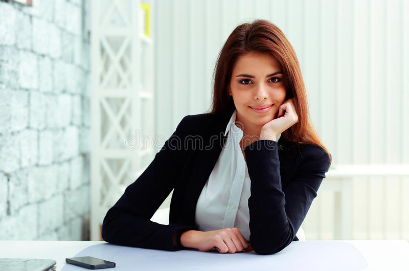 Young happy businesswoman sitting at the table on her workplace